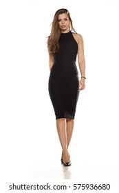 young woman in tight black dress walking on white background