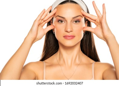 young woman tightening her face with her fingers on white background