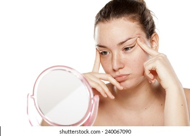 young woman tightens her eyes and eyebrows in the mirror