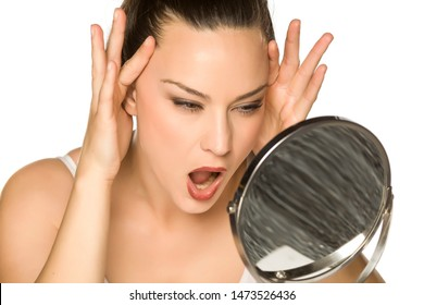 a young woman tightens her face with her hands on a white background