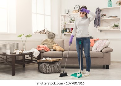 Young woman tired of spring cleaning house, sweeping floor with broom and scoop in messy room, copy space