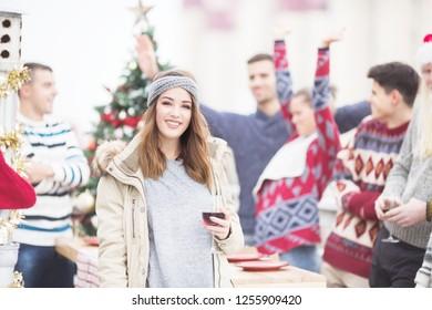 Young woman toasting for Christmas on balkony