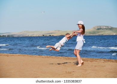 Young woman together with son summer on beach. mom and kid carefree playing on sand,coast sea, joy, fun. Happy family mother and child boy, lifestyle.