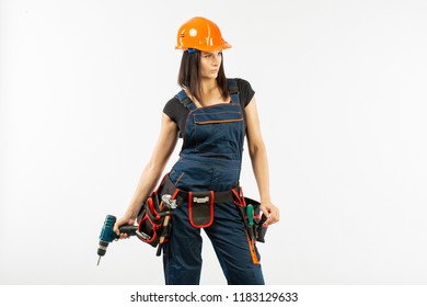 Young woman with toolbelt using driil and some power tools for her work at home. Girl working at flat remodeling. Building, repair and renovation.