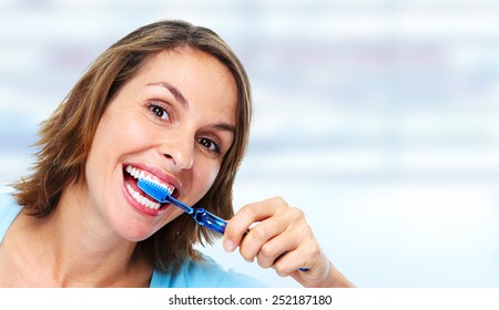 Young woman with toothbrush over blue medical background.