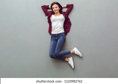 Young woman top view isolated on grey lying on floor relaxed looking amera smiling happy hands beside head