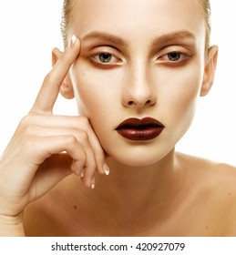 Young woman touching her face isolated on white background. Beauty portrait glamour girl with dark lips. Looking at camera.
