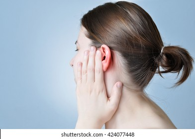 Young woman touching her inflamed ear