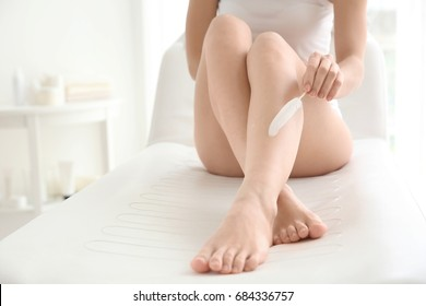 Young woman touching her leg with feather on couch. Epilation concept