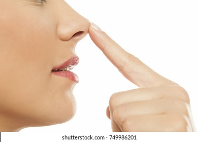 Young woman touching her nose with her finger