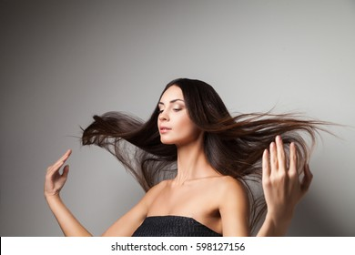 Young woman touching up her straight hair with hands. Horizontal studio shot.