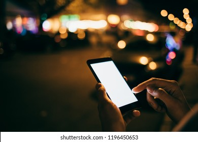 Young woman touching index finger on mock-up white screen smart phone on background bokeh light in night city. Close-up female using blank mobile device.