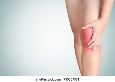 Young woman touching an inflamed knee with pain isolated with clipping path, Health care and medical concept.