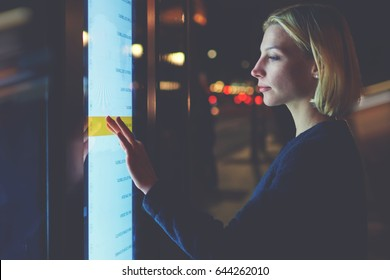 Young woman touching sensitive screen while selecting option on the list for find out schedule of city transport with smart stop bus in Barcelona, female standing at big display which reflecting light