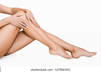 Young woman touching silky skin on legs after epilation, isolated on white background