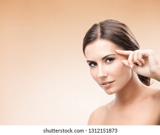 Young woman touching skin or applying cream, on color background, with blank copy space area for some advertising slogan or text message. Caucasian female model in beauty, skincare concept.