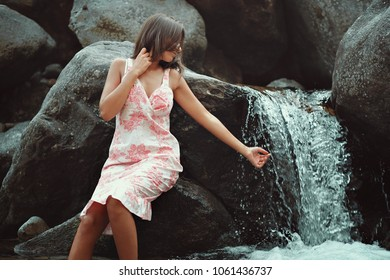 Young woman touching a waterfall. Summer dress