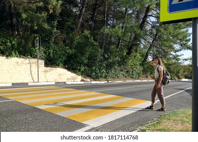 Young woman tourist with backpack crosses the road on pedestrian crossing in the suburbs on summer sunny day. There are signs on the side of the road and there are no cars