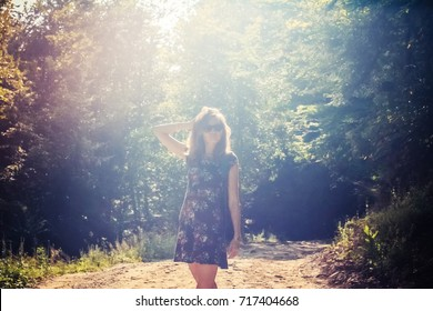 Young woman tourist with backpack in the forest in the backlight
