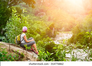Young woman tourist with backpack relaxing on top of the mountain and enjoying beatiful sunset.