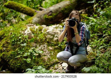 Young woman tourist with backpack taking photos of the beautiful landscape