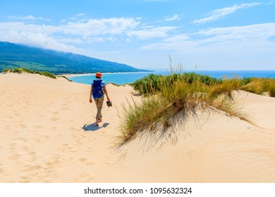 Young woman tourist with backpack walking on sand dune to Paloma beach, Costa de la Luz, Spain