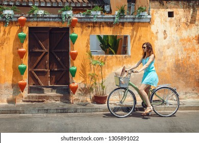 A young woman tourist  in a blue short dress rides a bicycle along the street of the Vietnamese tourist city of Hoi An. Girl on a bicycle against the yellow textured wall in Hoi An