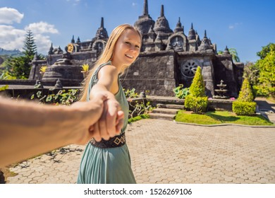 Young woman tourist in budhist temple Brahma Vihara Arama Banjar Bali, Indonesia Follow me concept