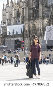 young woman tourist at Cologne Cathedral  and Square Roncalli in Cologne, Germany. The Dom - Roman Catholic Gothic cathedral, Koln Germany August 2017