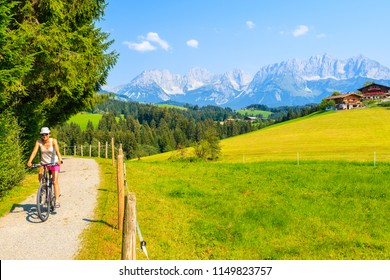 Young woman tourist cycling along green meadow in Gieringer Weiher mountain area, Kitzbuhel Alps, Austria