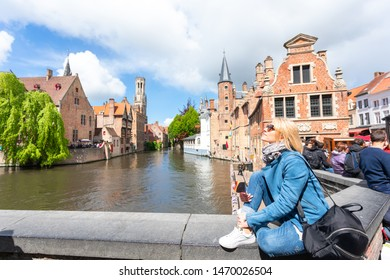 Young woman tourist with the flag of Belgium in the hands is enjoying the views of the city in the historic center of Bruges near the famous viewport. Travel to Belgium.