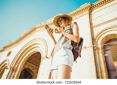 Young woman tourist in hat with backpack using gps navigation on phone. Online booking. Summer fashion style. City tour. Explore the world. Time to travel. Modern technology. Tourism concept. Yerevan