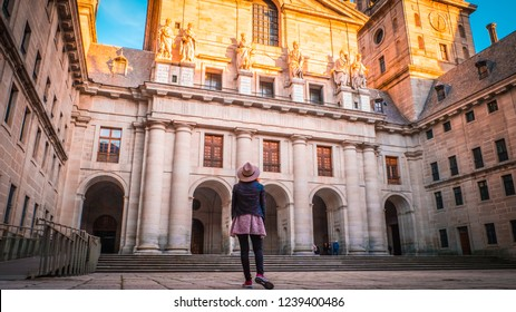 A young woman, tourist in a hat is standing in front of the basilica at El Escorial palace and monastery at the San Lorenzo de El Escorial during sunset. Famous kings residence near Madrid in Spain