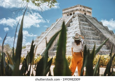 A young woman tourist in a hat stands against the background of the pyramid of Kukulcan in the ancient Mexican city of Chichen Itza. Travel concept.Mayan pyramids in Yucatan, Mexico