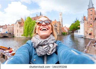 Young woman tourist is having fun, smiling and rejoicing while seeing the sights of Bruges, Belgium. Travel to Belgium. Happy girl makes selfie on the background of the famous viewpoint in the