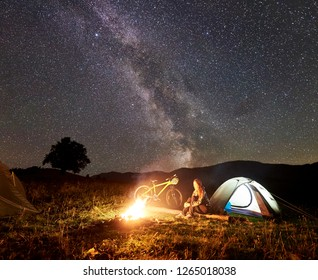 Young woman tourist having a rest at night camping near burning campfire, illuminated tourist tent, mountain bicycle under amazing beautiful evening sky full of stars and Milky way. Astrophotography