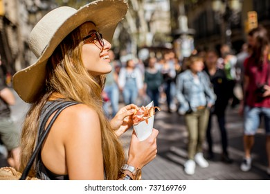 Young woman tourist holding jamon walking outdoors on the street in Barcelona city