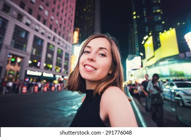 Young woman tourist laughing and taking selfie photo in New York City, Manhattan, Times Square. Female traveler and photographer takes selfie picture for her blog.