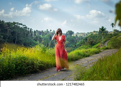 Young woman tourist in a lon red dress walking on the rainforest trail. Bali island. Indonesia.