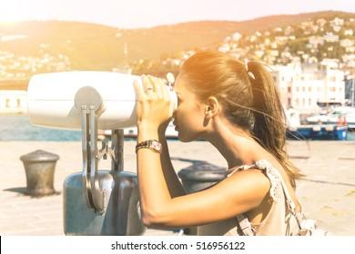 Young woman tourist looking through binoculars at horizon enjoying the beautiful sunny day - Outdoor portrait in summer