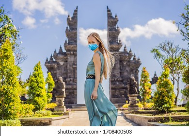 Young woman tourist in medical mask in budhist temple Brahma Vihara Arama Banjar Bali, Indonesia Tourists fear the 2019-ncov virus. Medical masked tourists