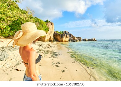Young woman tourist on the anse source agent beach and having fun. Vacations lifestyle concept on seychelles island