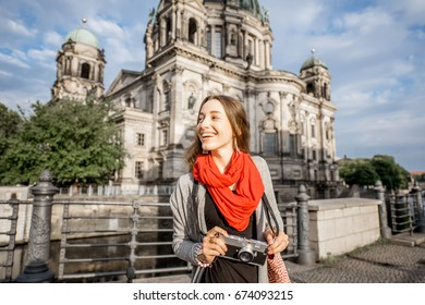 Young woman tourist with photo camera enjoying traveling in Berlin city walking near the famous cathedral