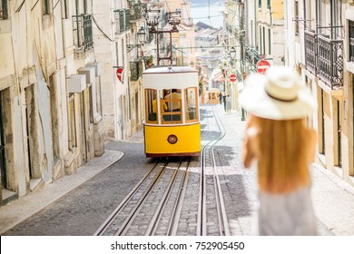 Young woman tourist photographing famous retro yellow tram on the street in Lisbon city, Portugal. Woman is out of focus