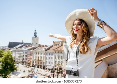 Young woman tourist pointing on the tower of Latin cathedral traveling in the old town in Lviv city, Ukraine