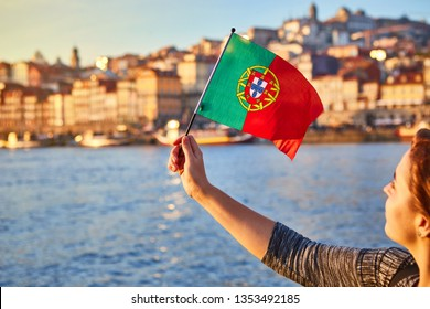 Young woman tourist with portuguese flag enjoying beautiful landscape view on the old town (Ribeira historical quarter) and river Duoro during the sunset in Porto city, Portugal
