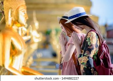 young woman tourist praying pay respect to Buddha statue in the palace temple in Bangkok of Thailand, Emerald Buddha Temple, Wat Phra Kaew, Bangkok Royal Palace popular tourist place