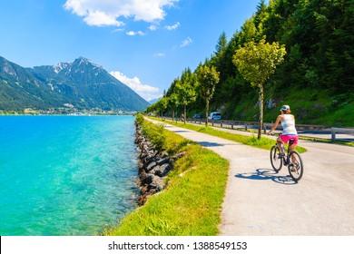 Young woman tourist riding bike along Achensee lake on sunny summer day, Pertisau, Tirol, Austria