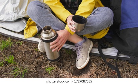 Young woman tourist sits near a tent and drinking tea from thermos. Camping in the forest