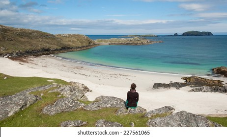 Young woman tourist sitting in front of a desert white beach with blue sea in the Isle of Lewis, Outer Hebrides, Scotland (UK)